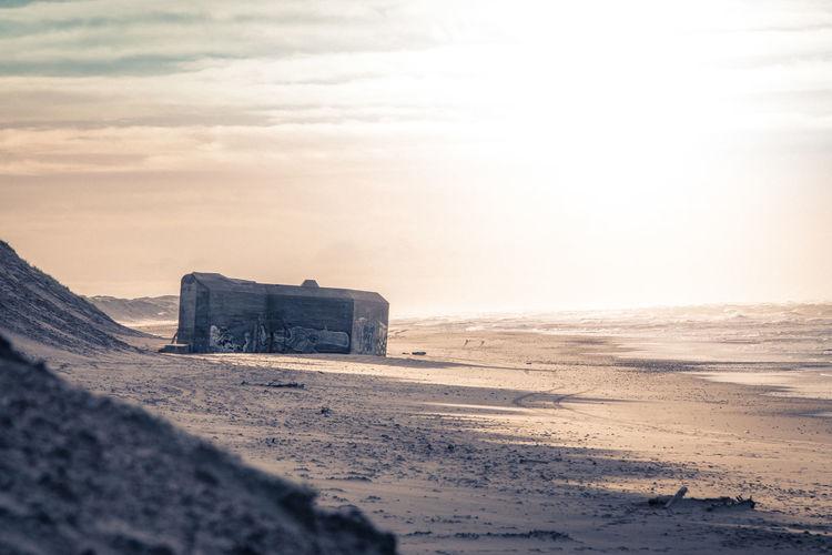 Bunker at sandy beach against sky