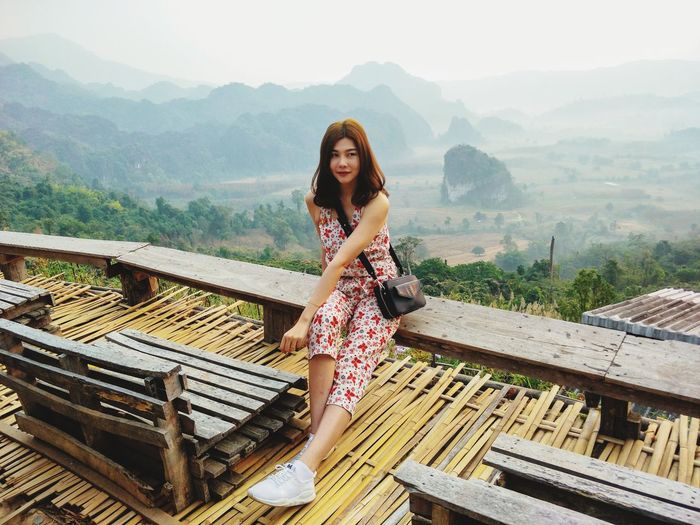 Full length of woman looking away while sitting against landscape