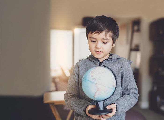 Cute boy holding globe while standing at home
