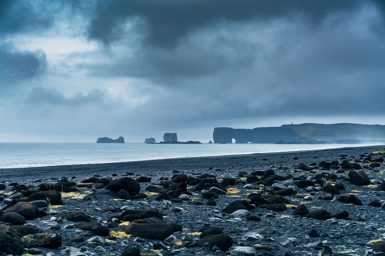 Low Angle View Of Rocky Beach Against Cloudy Sky