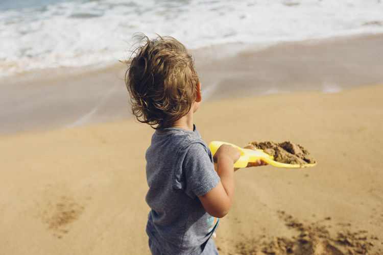 Rear view of boy holding sand at beach