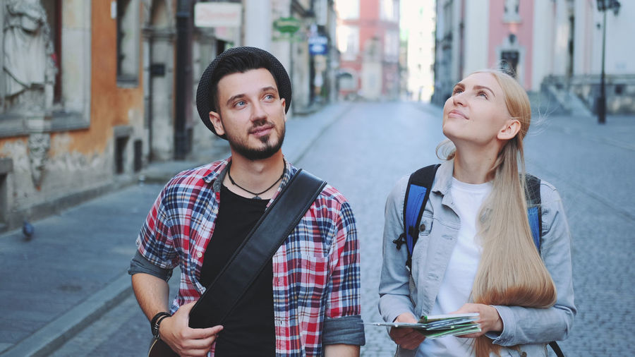 Man and woman holding map on footpath in city