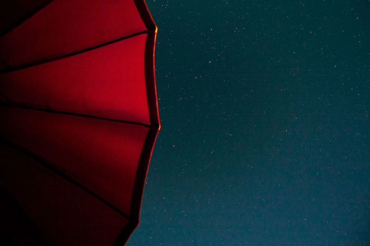 Low angle view of red parasol against sky at night