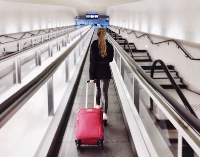 Full length of woman standing on escalator with suitcase in airport