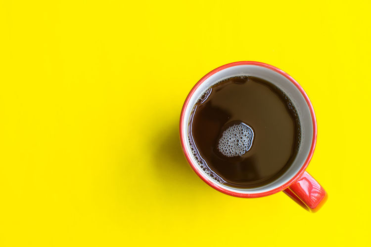 Drink Food And Drink Refreshment Cup Yellow Directly Above Coffee Freshness Mug Indoors  Coffee Cup Copy Space Colored Background Yellow Background Coffee - Drink Still Life Studio Shot No People Close-up High Angle View Non-alcoholic Beverage Crockery Black Tea Tea Cup