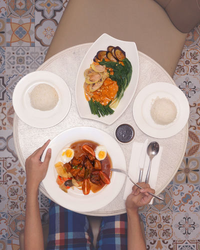 In-room dining for lunch at a boutique hotel. exotic tile patterns taken from above. Eating Adobo Breakfast Filipino Food Flat Lay Food Food And Drink Hotel Hotel Room Kare Kare Filipino Dish Leisure Activity One Person Plate Room Service Table Tiles Textures