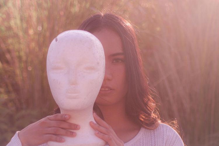 Portrait of woman holding statue