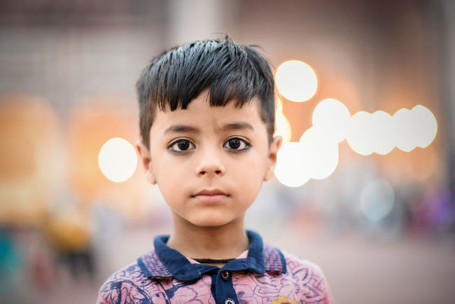 Portrait Focus On Foreground Headshot Childhood Men Child Males  Front View Boys One Person Illuminated Looking At Camera Close-up Real People Casual Clothing Innocence Black Hair Outdoors Contemplation Childeren Emotion Cute Cute Boy Child Portrait Eyes