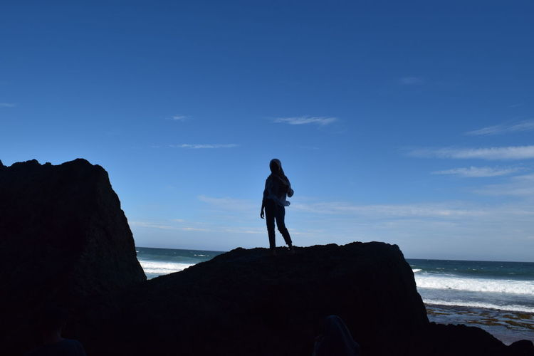 Full length of man standing on rock at beach against sky