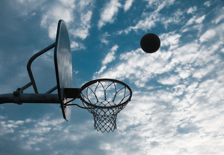 Low Angle View Of Ball In Mid-Air By Basketball Hoop Against Sky