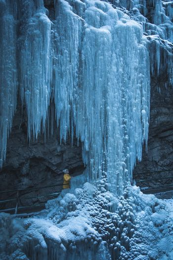 Woman by icicles in cave