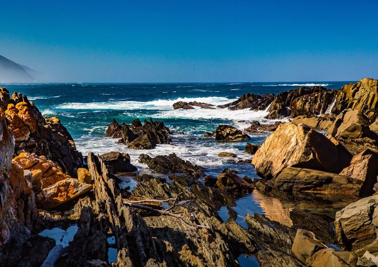 Panoramic shot of rocks on beach against clear blue sky
