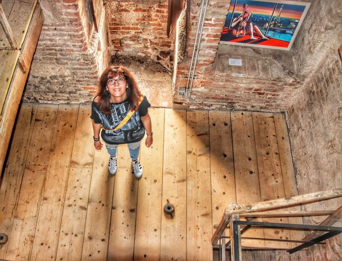High angle view portrait of smiling woman standing indoors