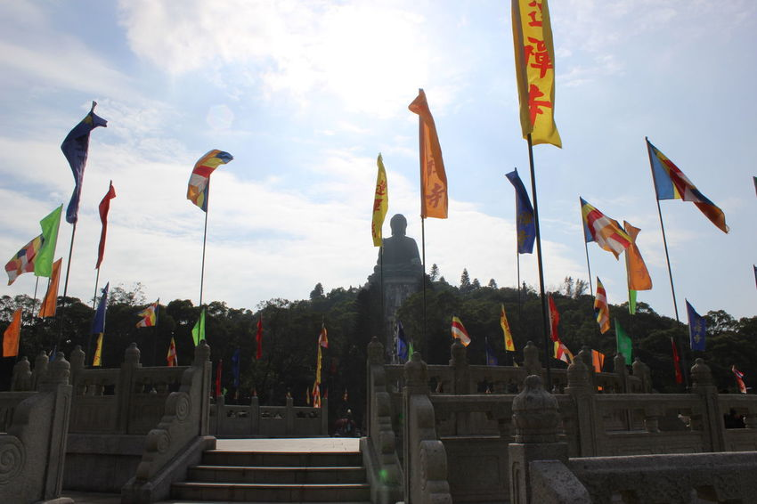 In A Row Flag Cultures Cloud - Sky City Outdoors Sky Day Low Angle View No People Tian Tan Buddha (Giant Buddha) 天壇大佛 HongKong Travel Destinations Travel Photography Sculpture Statue
