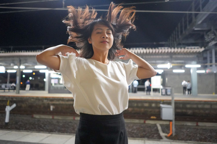 Young Woman Tossing Her Hair While Standing At Railway Station Platform