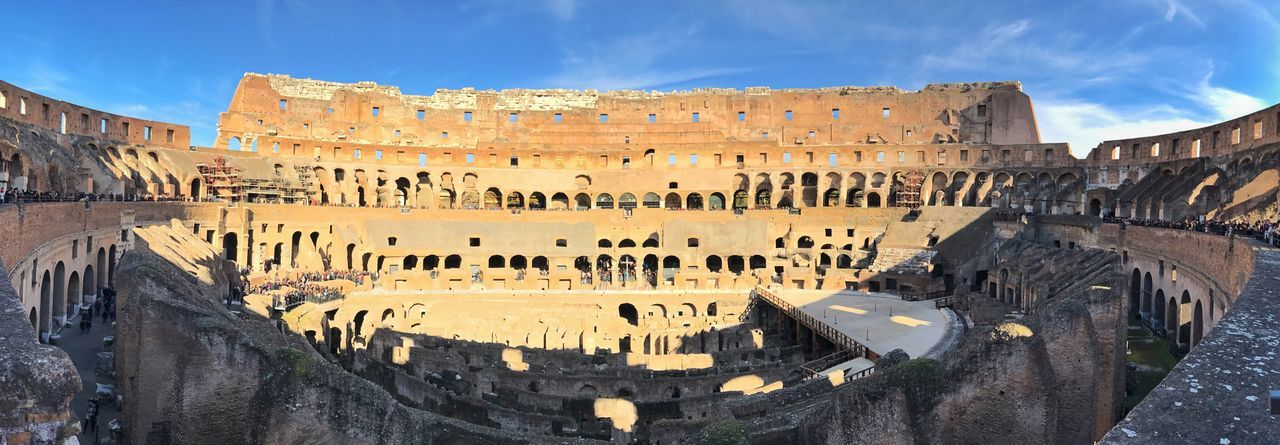 Panoramic view of colosseum against blue sky