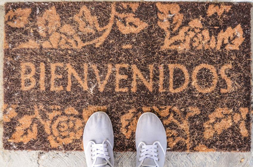 Welcome doormat with shoes Bienvenidos Carpet Decoration Door Doormat Doormats Enter Foot Get In High Angle View Home House House Door One Person Outdoors People Set Foot Shoe Sign Standing Step Text Welcome Welcome Doormat Welcome Sign