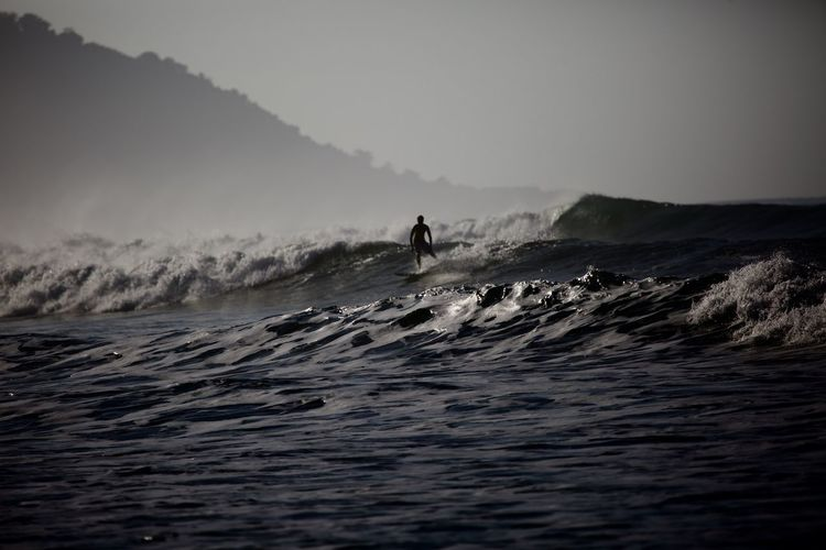 Water Sea Motion Wave Sport One Person Adventure Beauty In Nature Aquatic Sport Sky Leisure Activity Surfing Nature Waterfront Real People Unrecognizable Person Holiday Vacations Skill  Outdoors Horizon Over Water Power In Nature