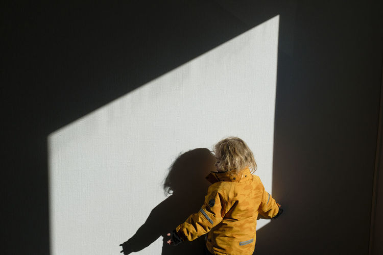 Rear view of girl standing against wall at home