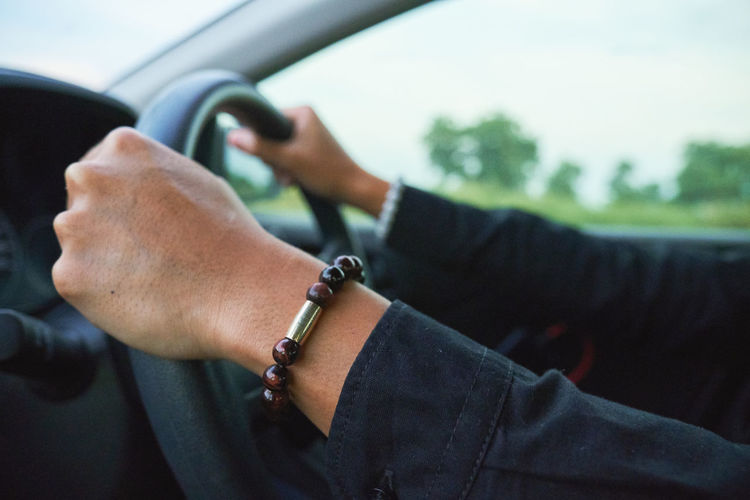 Cropped hand driving car