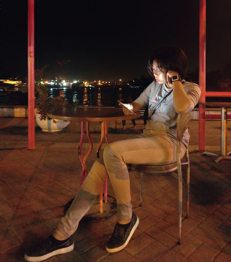 Woman sitting on table in restaurant at night