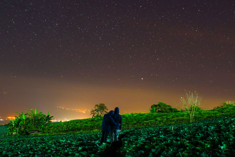 Rear view of couple standing against stars on field at night