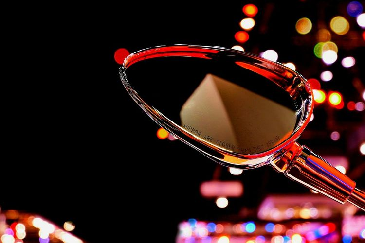 Close up of rear view mirror of motorbike with reflection on screen surface and multi color bokeh sphere shape with lighting decorations background on street night light Part Of Colorful Rear View Mirror Side View Object Moterbike Reflection Screen Bokeh Street Night Lighting Decoration Black Close Up Space Stainless Steel  Sphere Shape Circle Decoration Illuminated Close-up Christmas Decoration Nightlife