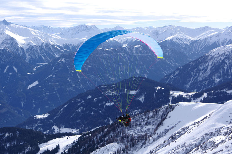 Man Paragliding Over Snowcapped Mountains