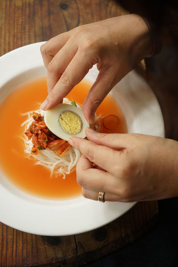 Cropped image of person having kimchi at restaurant