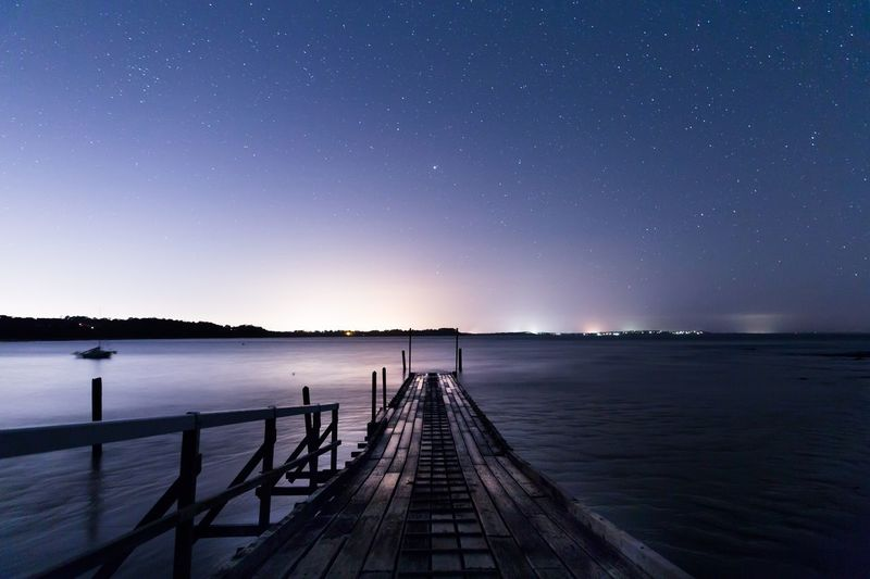 View of jetty in calm sea at night