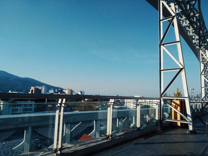 Bridge over bay against clear blue sky