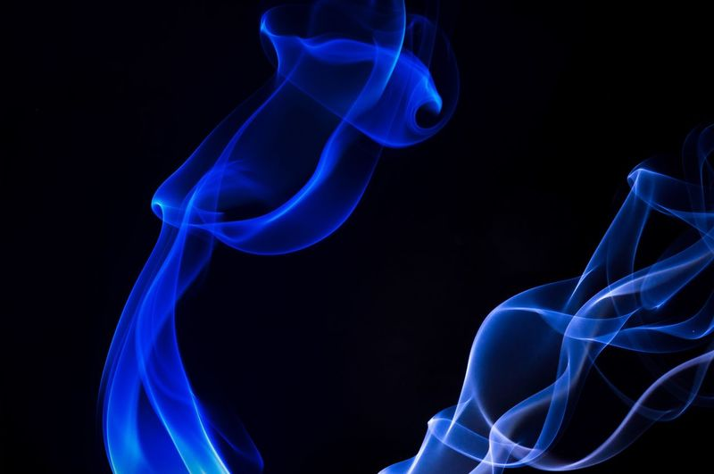 Close-Up Of Blue Smoke Against Black Background