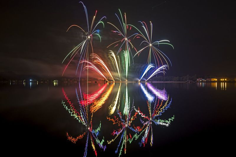 Reflection Of Firework Display In River At Night
