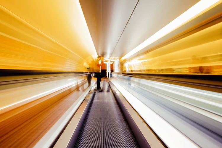 Blurred Motion Of People On Moving Walkway