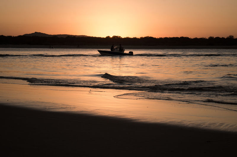 People in boat on sea against orange sky during sunset