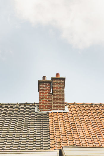 Architecture Brick Wall Building Exterior Built Structure Chimney Cloud Cloud - Sky Day Dual Exterior High Section Juxtaposition Low Angle View No People Outdoors Roof Roof Tile Sky Two