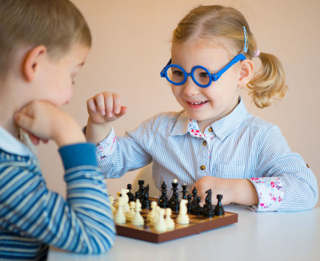 Cute sibling playing chess at home
