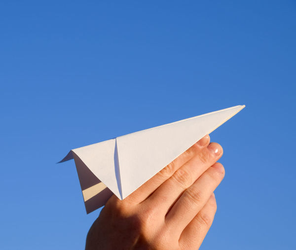 Close-up of hand holding paper against clear blue sky