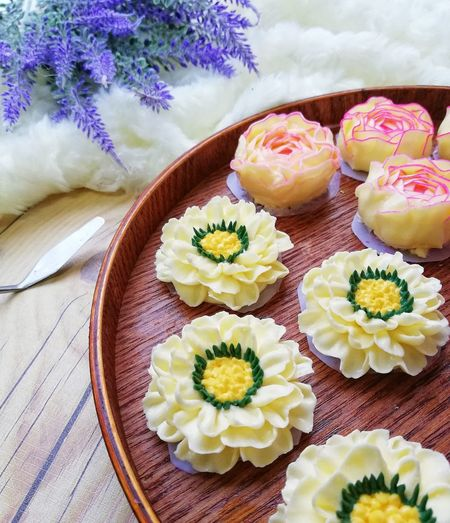 High angle view of sweet food made in floral pattern served on table