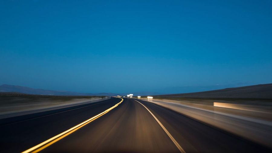 The Way Forward Transportation Road Road Marking Diminishing Perspective Speed Blue Journey Dividing Line No People Car Point Of View Clear Sky Motion Landscape Outdoors Nature Illuminated Day Nevada Desert