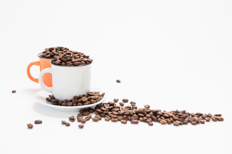 Coffee Cups Filled with Coffee Beans on a White Background Concept with Copy Space Food And Drink White Background Studio Shot Food Roasted Coffee Bean Indoors  Still Life Freshness Coffee - Drink Coffee No People Copy Space Cup Large Group Of Objects Brown Mug Close-up Refreshment Drink Wellbeing Crockery