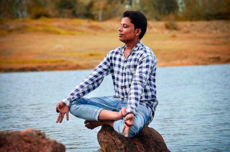 Man doing yoga while sitting on rock at lake