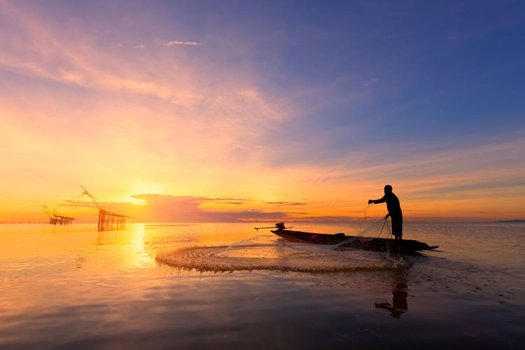 Silhouette of man fishing against sky during sunset
