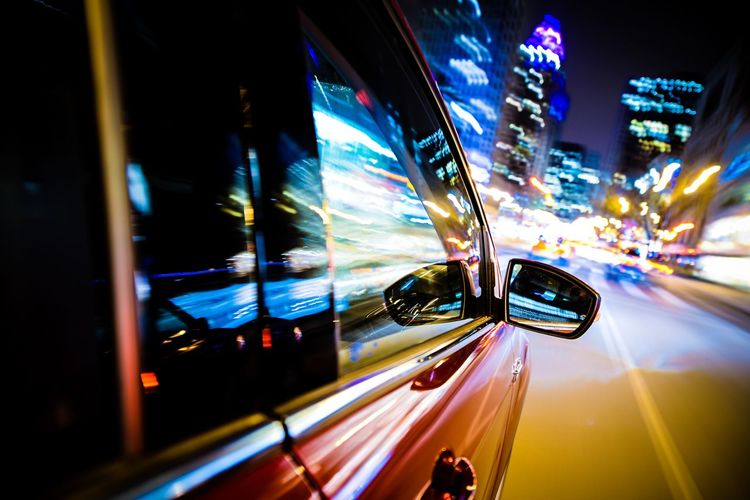 Car moving on road in illuminated city at night