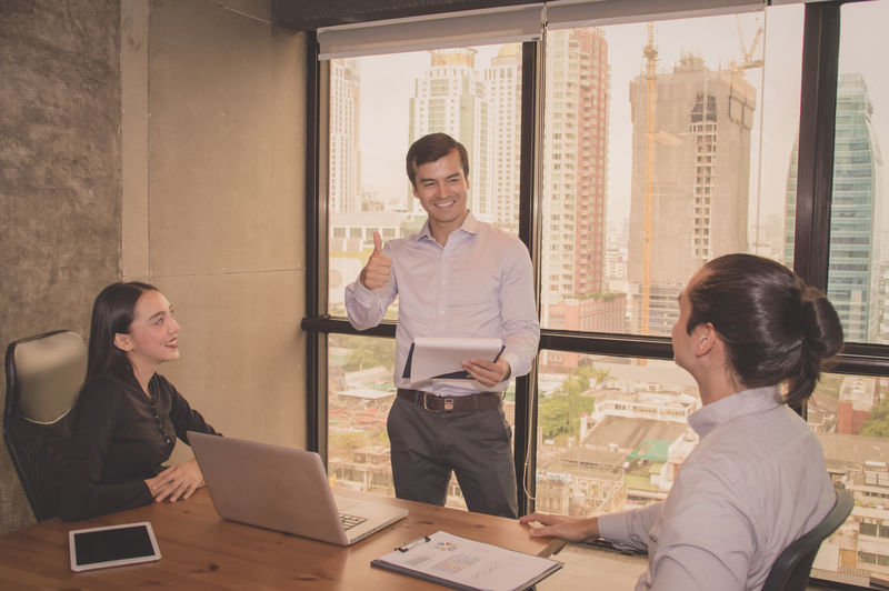 Smiling businessman gesturing thumbs up while discussing with colleagues during meeting in office