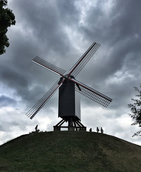Low Angle View Of Windmill On Hill Against Cloudy Sky