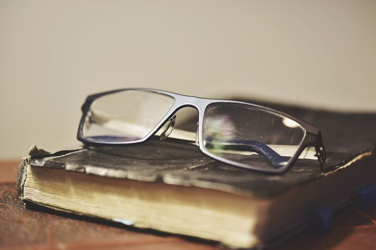 Close-up of eyeglasses with book on table