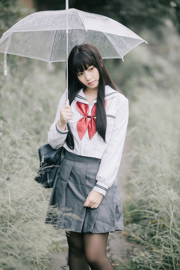 Young woman standing on field during rainy season