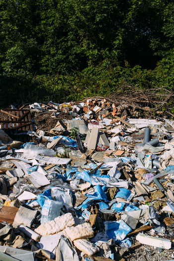 Stack of garbage by trees in forest