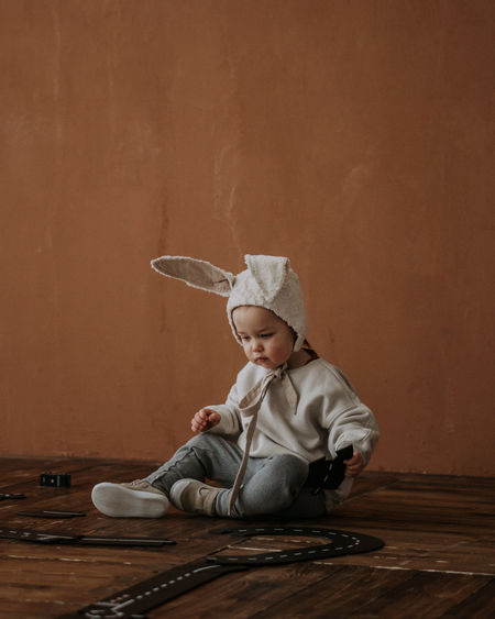 Toddler baby boy in funny bunny hat playing with toy car